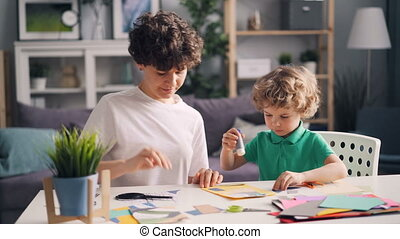 Little boy and his mom making collage cutting paper figures sticking with glue
