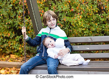 Little boy and his newborn baby sister relaxing on a wooden swin