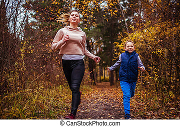 Little boy and his sister running in autumn forest