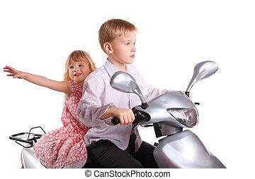 little boy and joyful little girl is sitting on motorcycle. isolated.