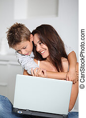 Little boy and mother sitting on sofa at home with laptop