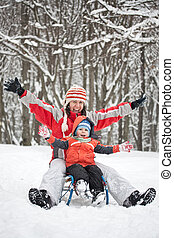 Little boy and mother sliding