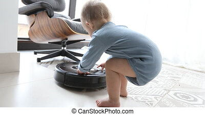 little boy and robot vacuum cleaner on the floor