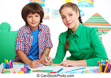 Little boy studying with young teacher in a preschool center for children. Teacher drawing picture with boy and looking at camera