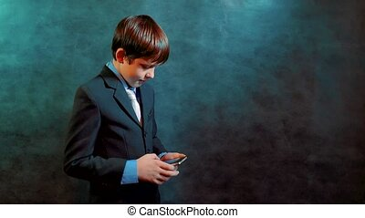 little boy as a businessman holding a smartphone writing a message in social media.