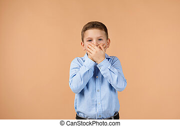 child closes her mouth with his hand