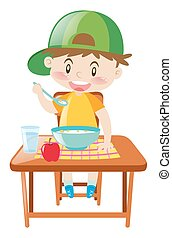 Little boy at dining table eating breakfast