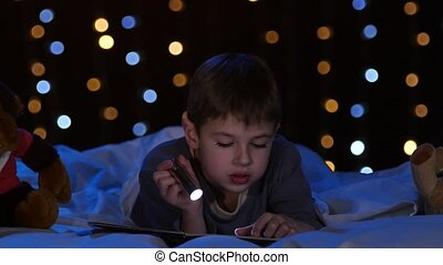 Little boy at night reading a book on the bed. Bokeh background