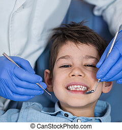 Little boy at regular dental check-up - Dentist doing ...