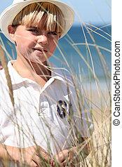 Little boy at the beach wearing hat