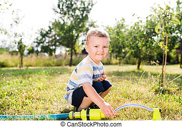 Little boy at the sprinkler having fun, summer garden