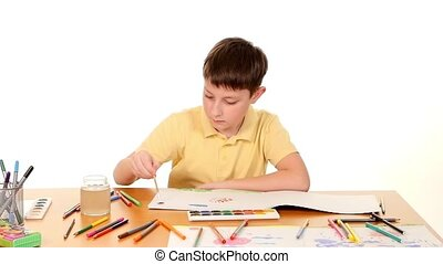 Little boy at the table drawing with felt-tip pen on white background, slow motion