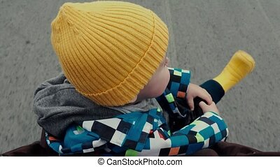Little boy baby carriage in yellow hat and boots - From...