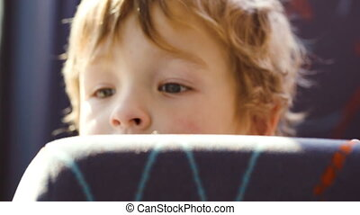 Little boy behind the seat in the bus