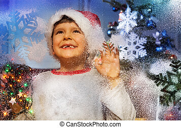 Little boy behind window with snowflake smiling
