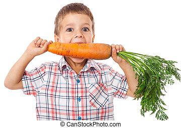 Little boy biting the carrot