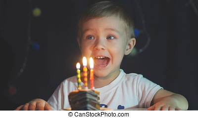 Little boy blowing candle on birthday cake.