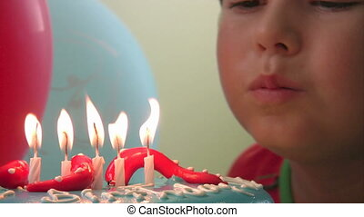 Little boy blowing his birthday can