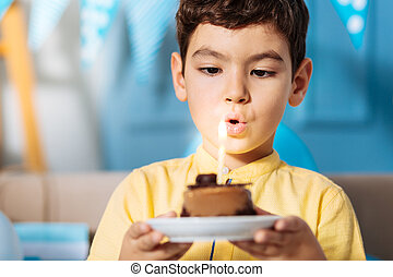Little boy blowing out candle and making birthday wish