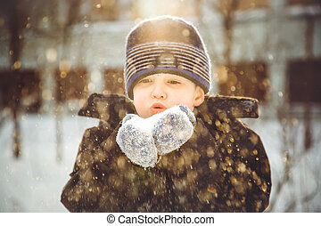 Little boy blows snow with mittens on bokeh background of snowflakes.
