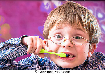 Little boy brushing teeth with a toothbrush