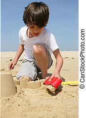Little boy building a sand castle