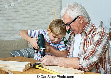 Little Boy Building Birdhouse with Grandpa