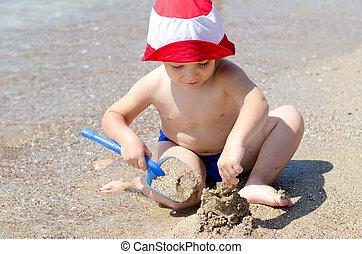 Little boy building sand castles