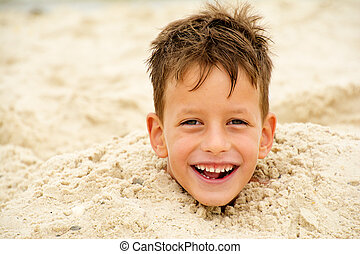 little boy buried in the sand on beach