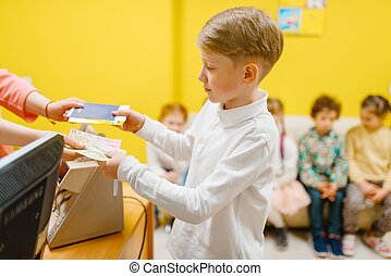 Little boy buying ticket in playroom
