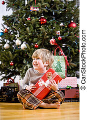 Little boy by Christmas tree holding present