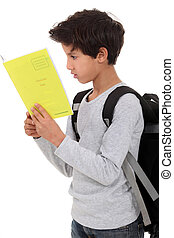 Little boy carrying backpack and reading book