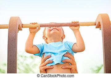 Little boy catch up on the horizontal  bar