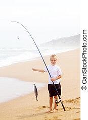little boy catching a big fish on beach