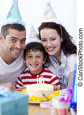 Little boy celebrating his birthday with his parents