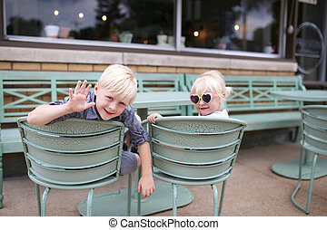 Little Boy Child and HIs Baby Sister Sitting at Cafe Table Outside Trendy Coffee House