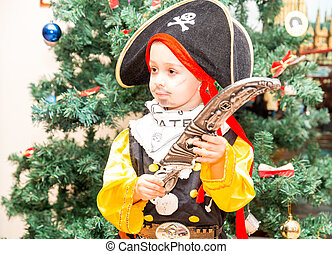 Little boy child dressed as pirate for Halloween  on background of Christmas tree. Kid in carnival costumes for Christmas
