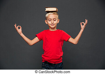 Little boy child meditate with book on head.