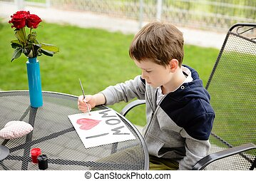 Little boy child painting greeting card for his mother