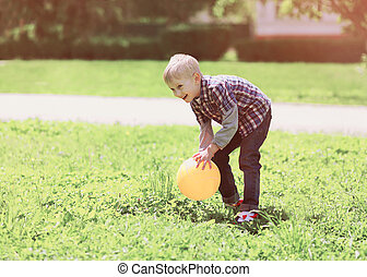 Little boy child playing with ball outdoors on the grass in summer day