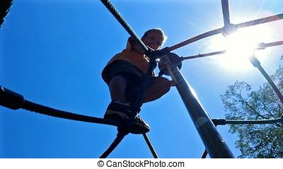 Little boy climbing a rope pyramid against the sun