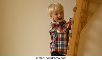 Little Boy climbing ladder in the kindergarten indoors