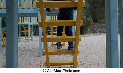 Little boy climbs stairs on playground outdoor. Smiling...