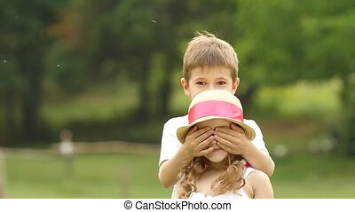 Little boy closes his eyes to the girl with his own hands. Slow motion