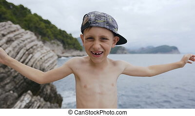 Little boy closing and discover his eyes with his hands. Portrait of a happy kid in cap on the sea background