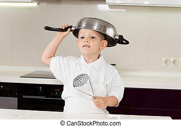 Little boy clowning around with kitchen utensils