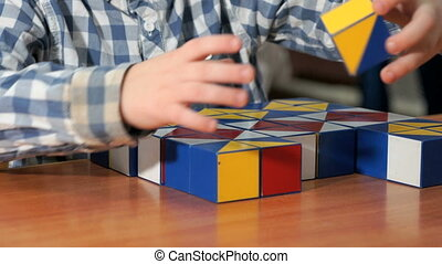 Little boy collecting pattern using colored cubes - Close-up...