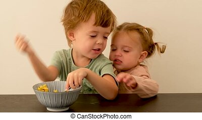 Little boy communicating with capricious sister during breakfast