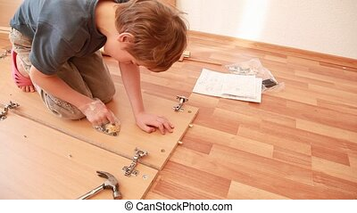 Little boy construct piece of wooden furniture on floor