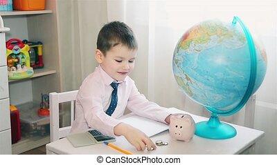 Little boy counts his savings on a calculator HD